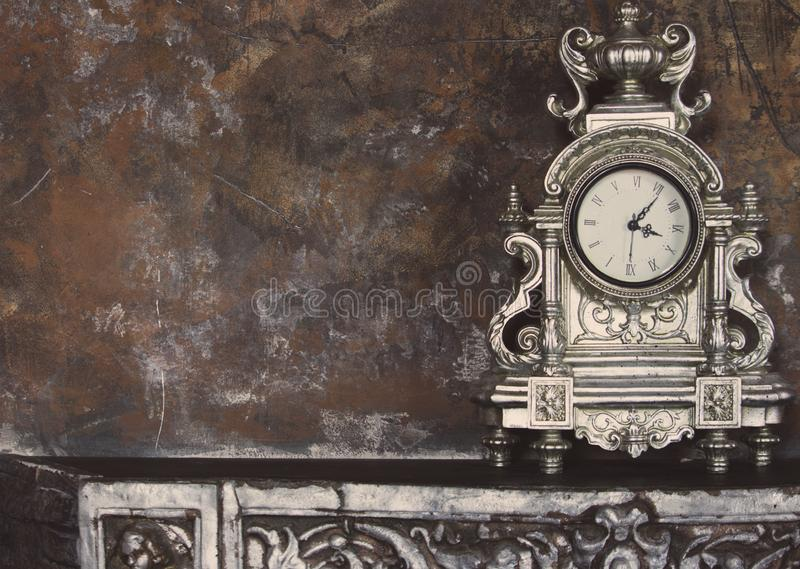 Old metal clock on shelf against grunge wall. Time concept. Old vintage clock. royalty free stock photo