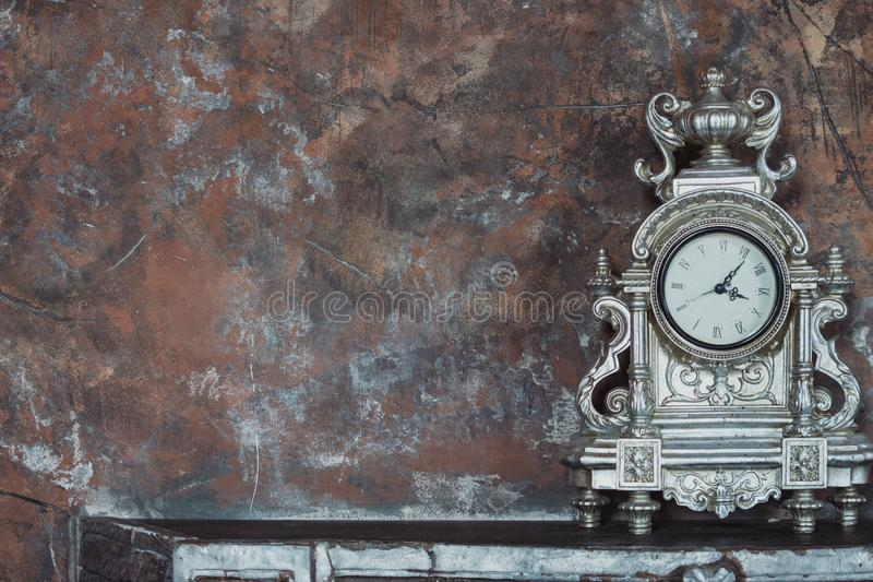 Old metal clock on shelf against grunge wall. Time concept. Old vintage clock. Old metal clock on shelf against grunge wall. Time concept. Elegant clock on aged stock images