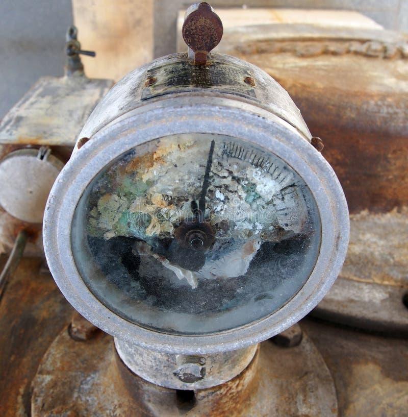 Old broken rusty gauge mounted on industrial machinery. An old metal corroded broken rusty gauge mounted on industrial machinery stock images