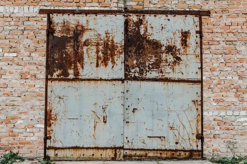 Old metal door from the garage. Rusty. Garage old red bricks. Ba royalty free stock image