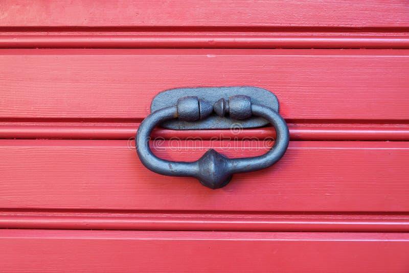 Old metal door knocker. On a wooden door royalty free stock photography
