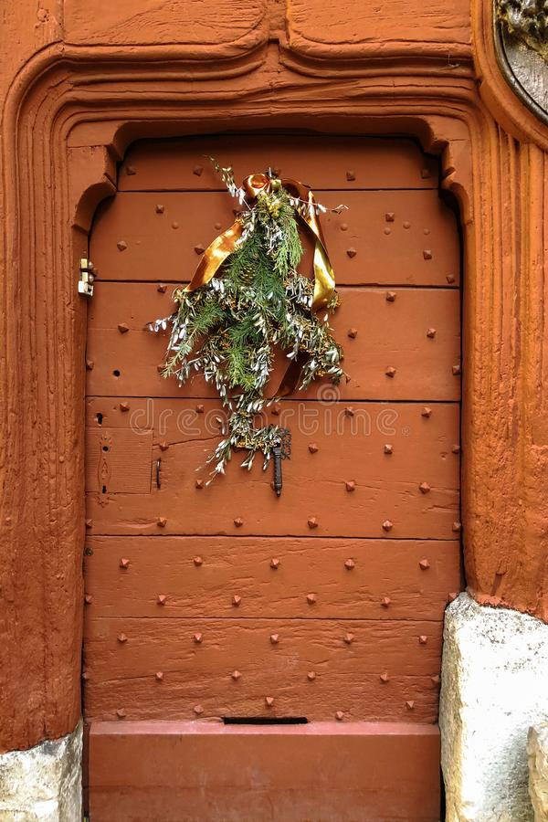 Old metal door with studs in the shape of a pyramid with a christmas decoration stock image