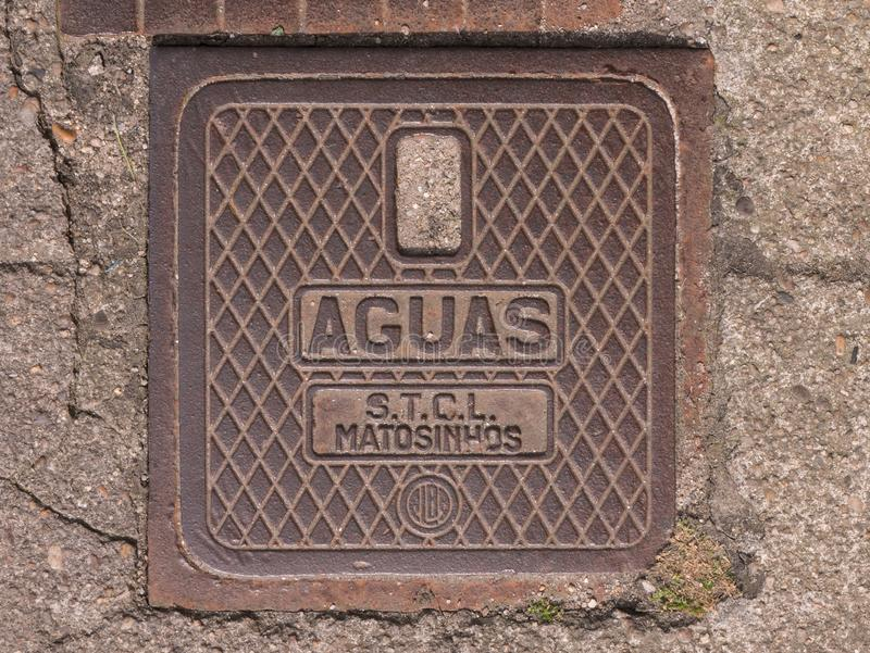 Old metal drain cover in Povoa de Varzim, Portugal with AGUAS lettering and crosshatch pattern. Shot from above stock photography