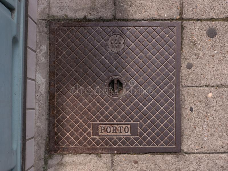 Old metal drain cover in Povoa de Varzim, Portugal with IMJBI Porto letters stock images