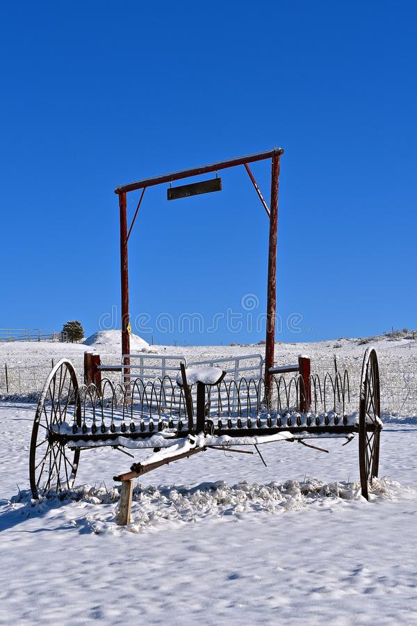 Old metal dump rake left in the snow at a ranch setting. An old steel dump rake after a snowfall in a ranch setting royalty free stock photo
