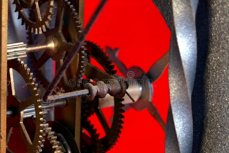 Old metal dusty mechanical clock with moving gears and screws. Brass cog wheels, Close view of old rusty clock mechanism. With gears and cogs. Element of design royalty free stock photography