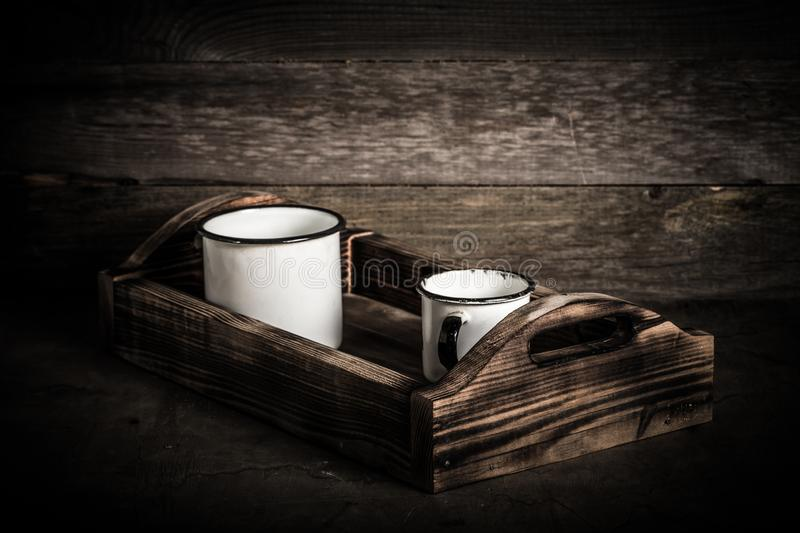 Old metal enamelware and handmade wooden box on the retro table. Toned stock photo