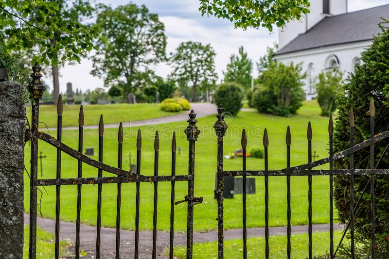 Old metal entrance gate to an old cemetery in Sweden stock photography