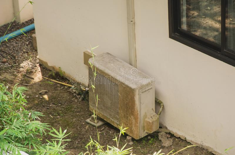 Old metal exterior fitted air conditioning unit staying on the ground needing maintenance. Old dirty metal exterior fitted air conditioning unit staying on the royalty free stock photography