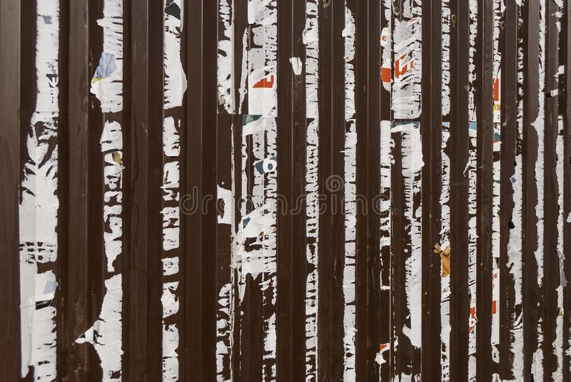 Old metal fence with the remains of previously pasted ads on it. Abstract background royalty free stock photo