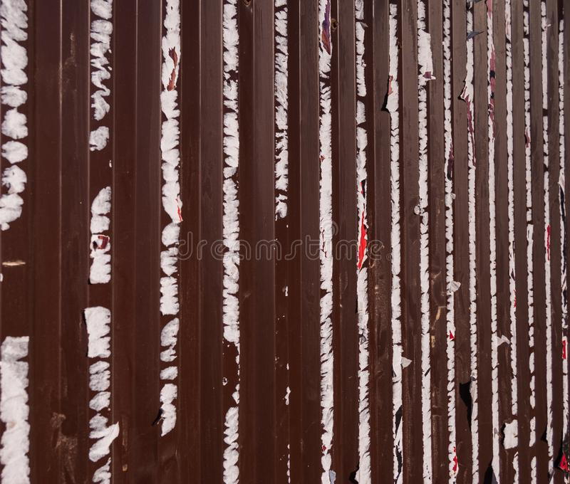 Old metal fence with the remains of previously pasted ads on it. Abstract background stock photos