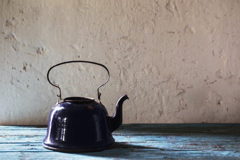 Old metal kettle on grunge background stock image