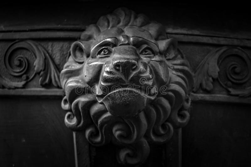 Old metal lion head decoration. Architecture detail of vintage door. Lion face knob closeup. Animal head at entrance of stock photography