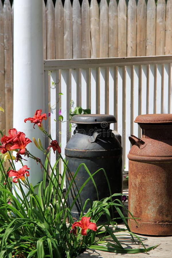 Old metal milk jugs on wood stoop. Old, rusty black and brown metal milk jugs on wood stoop of rural country home royalty free stock photos