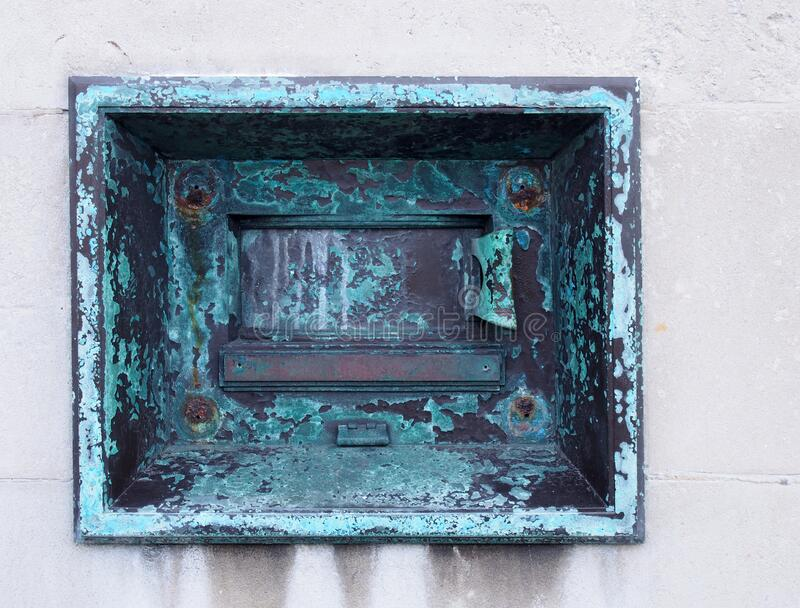 Old metal outdoor overnight deposit box also known as a night safe, once common on the outside walls of banks royalty free stock image