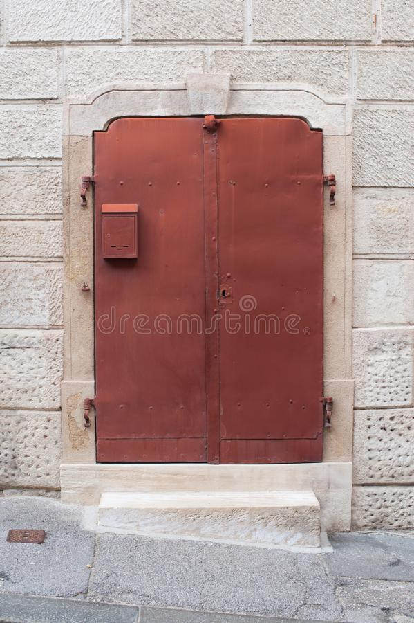 Old metal red doors in a stone wall, house. Red metal doors with small mailbox. Exterior design. Wall made of stone, marble royalty free stock photos