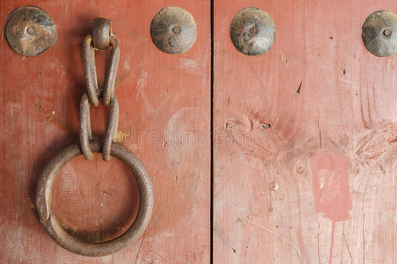 Old metal ring handle on red wooden door stock photo