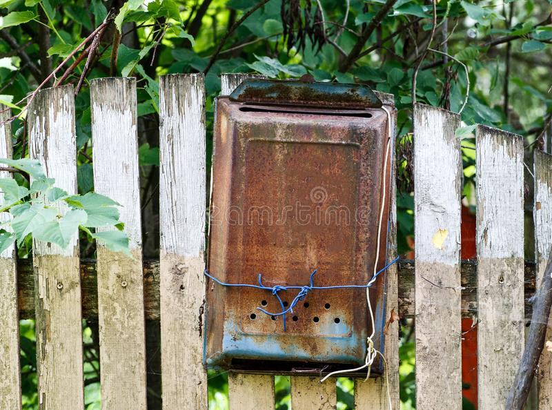 Old metal rusted mail box hanged on a wooden fence under green tree royalty free stock photography