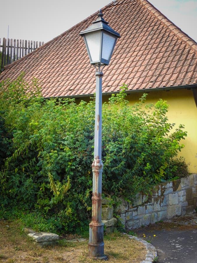 Old metal street lamp in the village. Old metal and rusty street lamp in the village royalty free stock photos