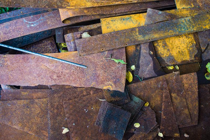 Old metal scrap on scrap-heap. Old rusty metal plates with different color on a scrap-heap with some grass beneath royalty free stock photos
