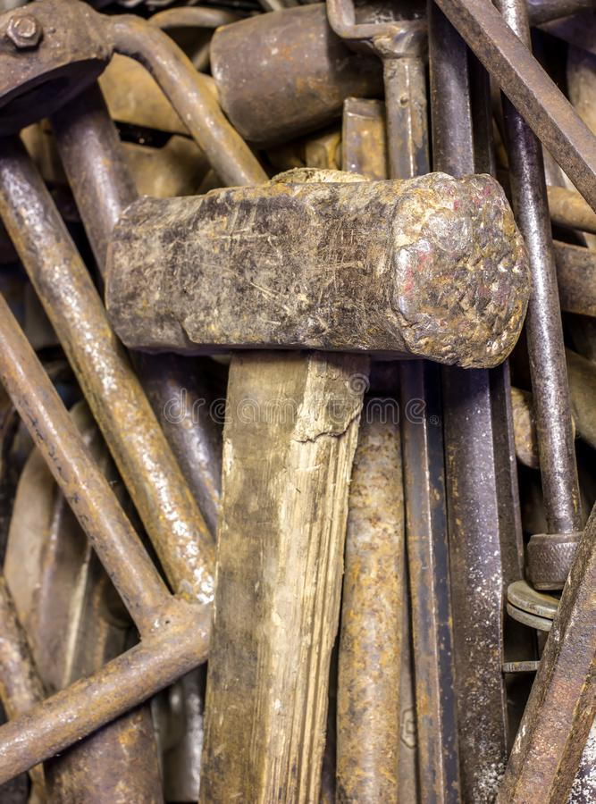 Old metal sledgehammer with a wooden handle lies on a pile of rusty tools stock images