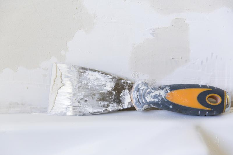 Old metal spatula with color and rust in front of a plaster wall stock photos