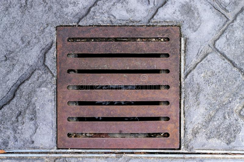 Old metal water sewer cover top view stock photography