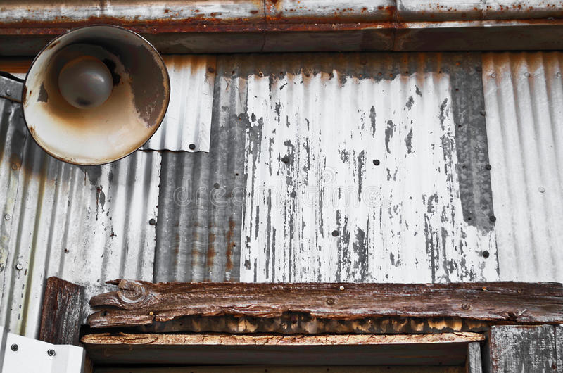 Old metal wall and vintage lamp. A vintage bell lamp mounted on a rusting metal wall of an abandoned warehouse royalty free stock image