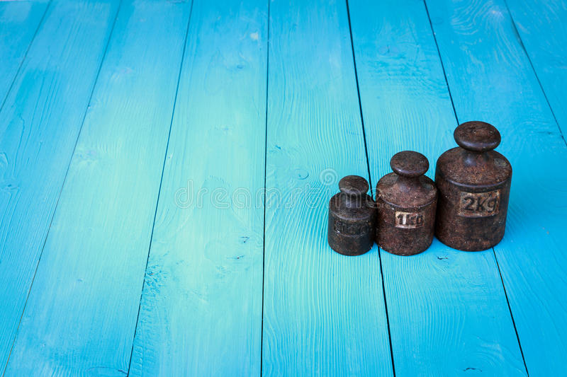 Old metal weights on vintage boards background stock images