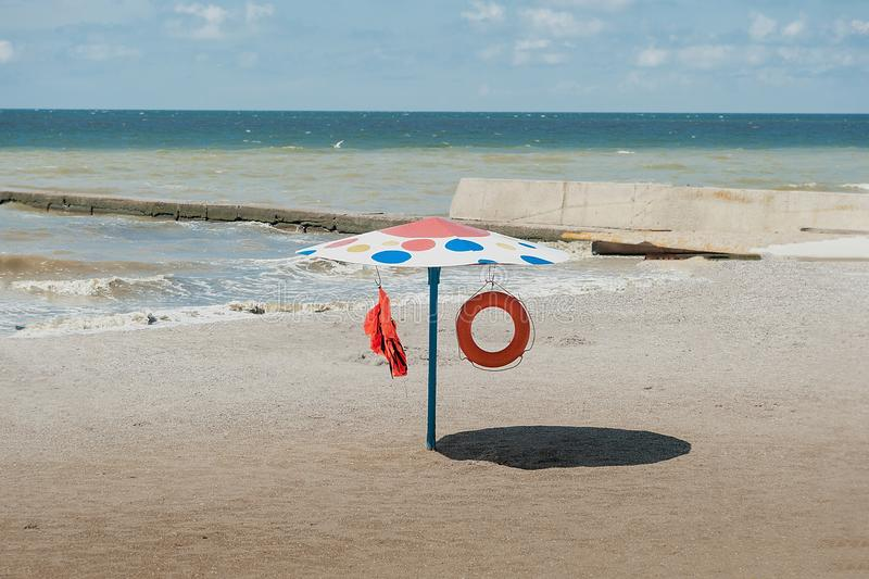 Umbrella with life buoy and vest standing on the beach. Old metall umbrella with life buoy and vest standing on the beach. rescue station at sea. Black sea royalty free stock photos