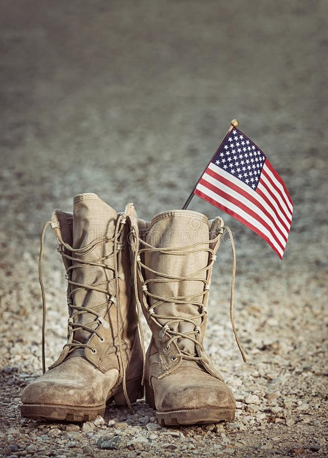 Old military combat boots with the American flag. Rocky gravel background with copy space. Memorial Day or Veterans day concept. Vintage tone stock image