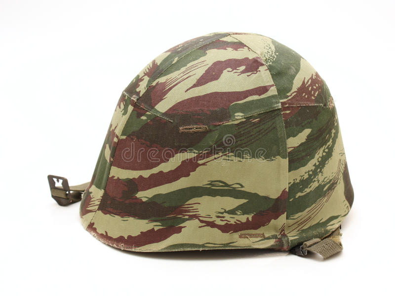 Old military helmet, side view. Image of an old military helmet with a camouflage fabric worn on top, viewed from the side royalty free stock image