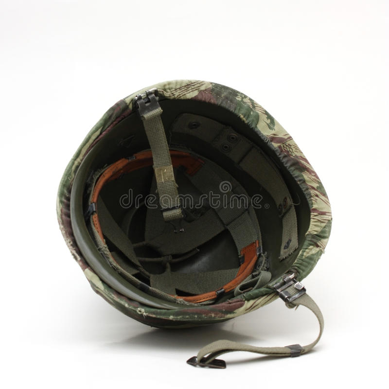 Old military helmet toppled over. Image of an old military helmet with a camouflage fabric worn on top, toppled over stock photo