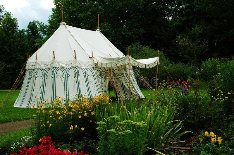 Old military tent. In a flowered environment stock photos