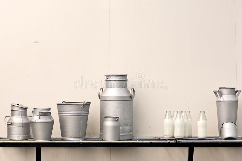 Old milk jugs. Cans, bottles and bucket stock image