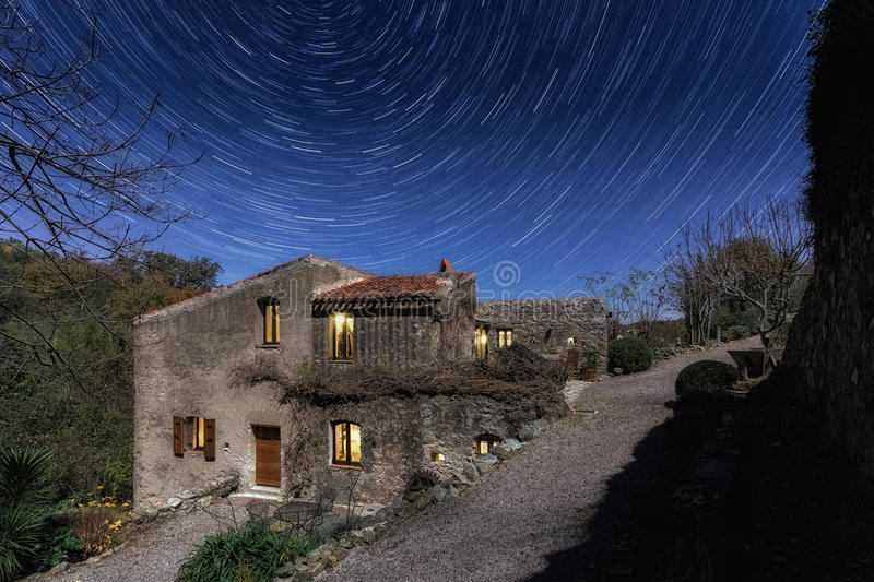 Old mill in Corsica at night with star trails above stock photos