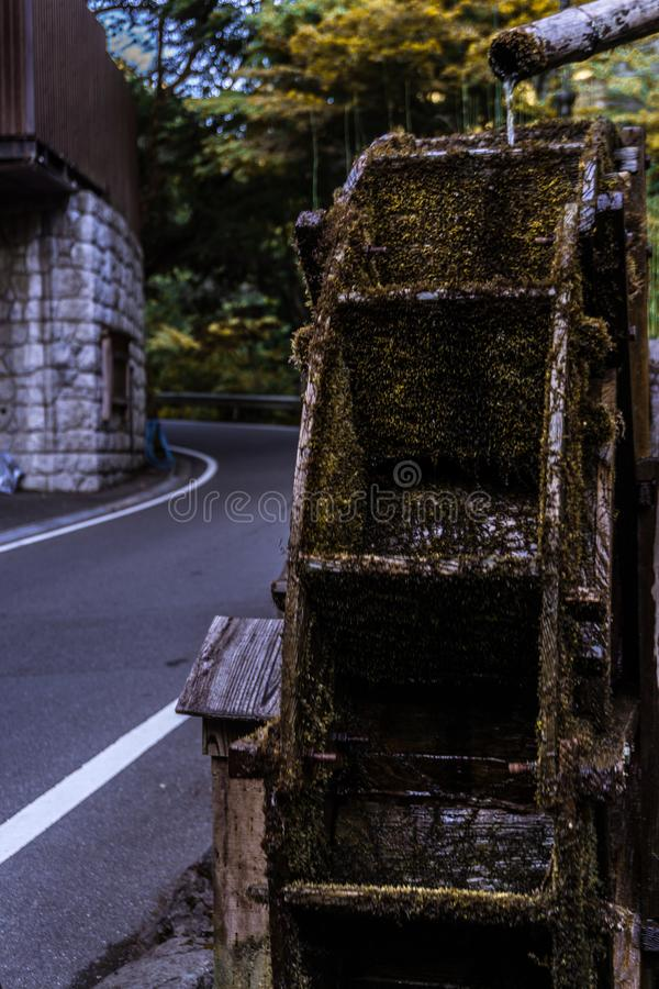 Wooden wheel full of moss because of the pass of time and water forgotten and rotten. Old mill full of moss stock photo