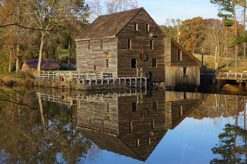 Old mill with holiday wreath reflecting in a pond. stock image