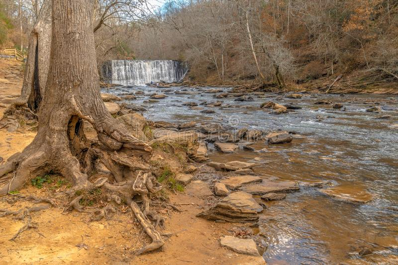 Old Mill Park, Roswell, Georgia USA. Two people photography the falls up close on the rocks, photo taken when the water level was low as the trees roots were stock photo