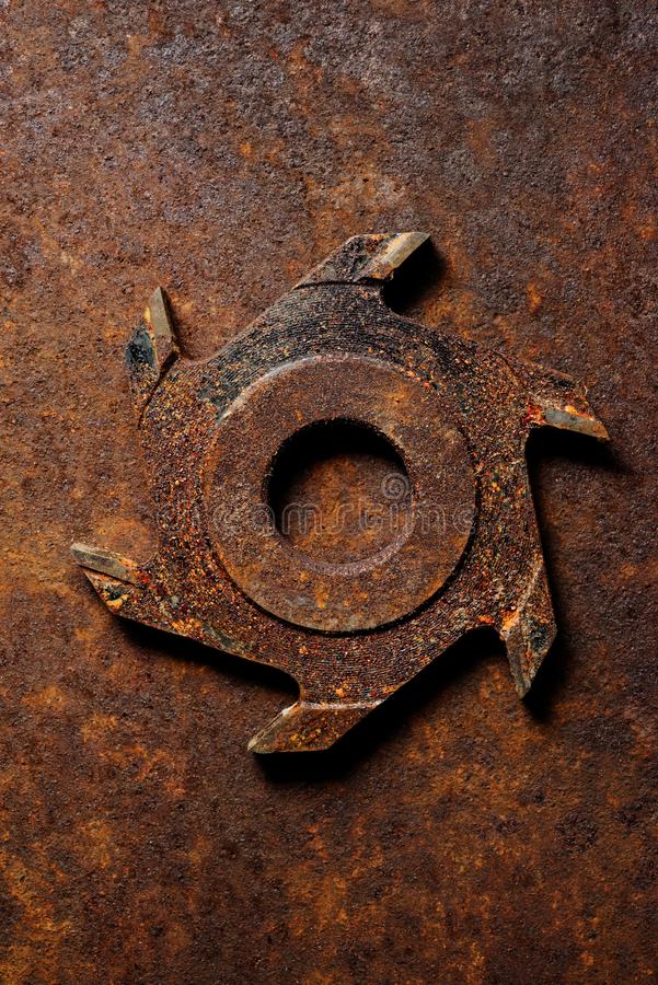 Old milling cutter on rusty metal background stock image