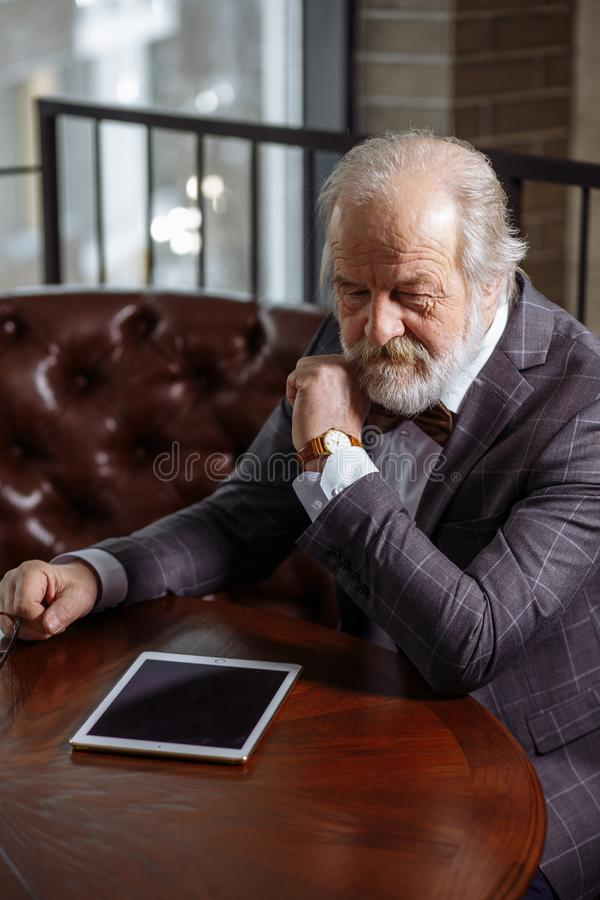 Old millionaire with contemplative look royalty free stock images