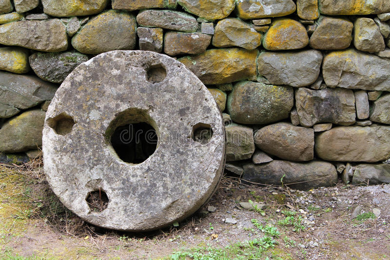 Old millstone on a background of stone wall, Etar, Bulgaria royalty free stock photo