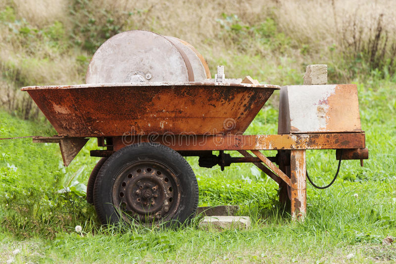 Old millstone. An old mill orange in a green meadow. In construction, characteristic kneading machine mostly used as the packaging of the pozzolanic mortars royalty free stock image