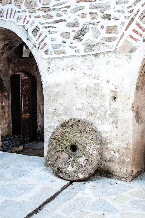 Old millstone standing near a stone wall royalty free stock photo