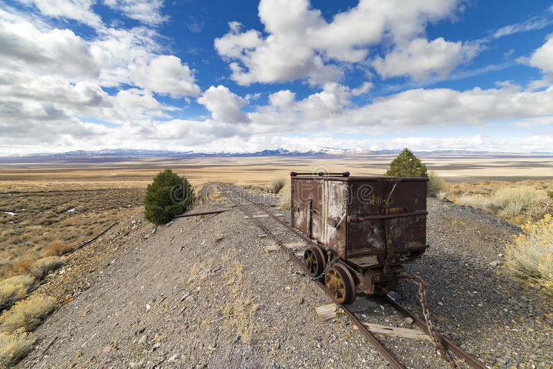 Old mining ore cart on tracks underneath a beautiful blue sky royalty free stock photos