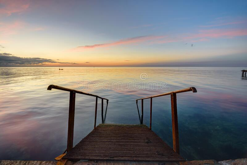 The old mittal staircase on the pier descends into the sea, against the background of the evening beautiful sunset. The old mittal staircase on the pier descends royalty free stock photos
