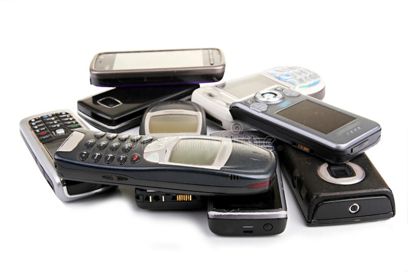 Old mobile phones. Image of broken old cell phones sitting on a table top royalty free stock photography