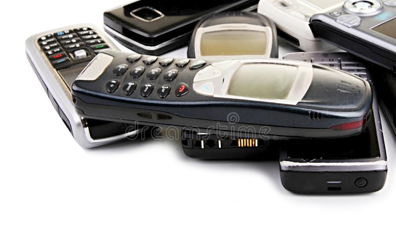 Old mobile phones. Image of broken old cell phones sitting on a table top stock photography