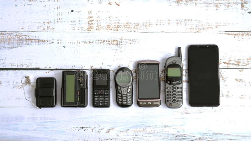 Old mobile phones and pagers isolated on white wooden background stock images