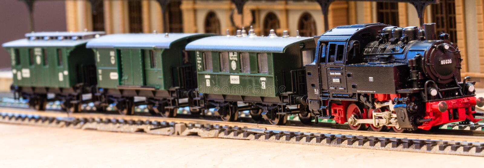 Old model train in front of a toy station stock images